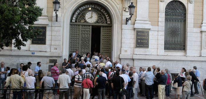 Customers wait outside a bank in Athens, Greece