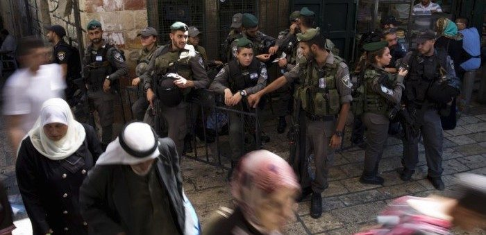 Palestinians walk past Israeli police after Friday prayers outside Damascus Gate in Jerusalem's Old City