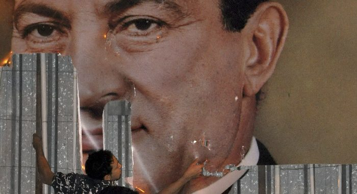An anti-government protester defaces a picture of President Hosni Mubarak in Alexandria, Egypt, Jan. 25, 2011. Stringer/Egypt/Reuters/Corbis
