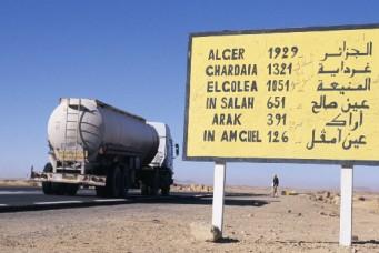 Truck passing road sign in Tamanrasset, Algeria. Frans Lemmens/Corbis