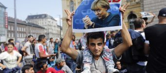 Man holds poster of German Chancellor Angela Merkel during march of refugees fleeing Hungary