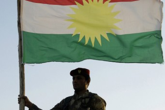 A Kurdish peshmerga soldier holds a Kurdistan flag in the northern Iraq, Ninawa province, Aug. 6, 2012. Azad Lashkari/Reuters