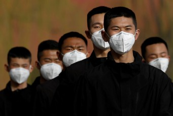 Security personnel wearing face masks to contain the spread of coronavirus disease (COVID-19) walk along a street outside Forbidden City in Beijing, China March 18, 2020. REUTERS/Carlos Garcia Rawlins TPX IMAGES OF THE DAY - RC2CMF9VZ6A9